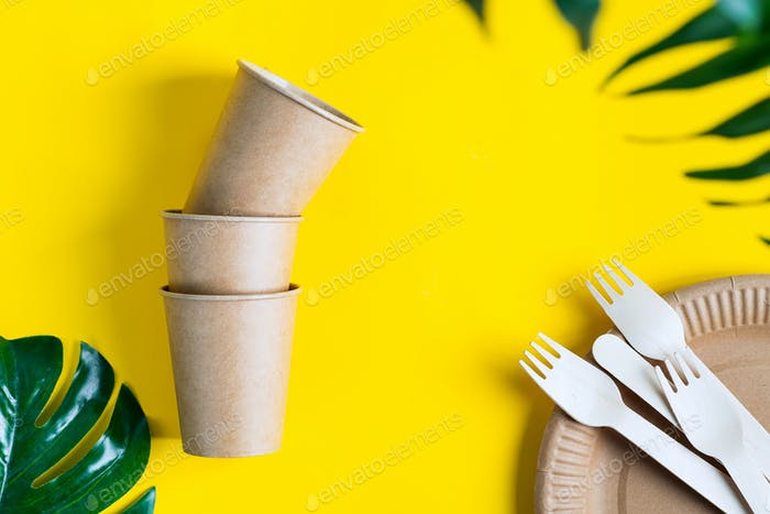 Set of eco friendly disposable tableware made from paper and wood on a yellow background with green
