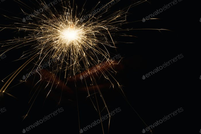 New year party sparkler in female hands on black background