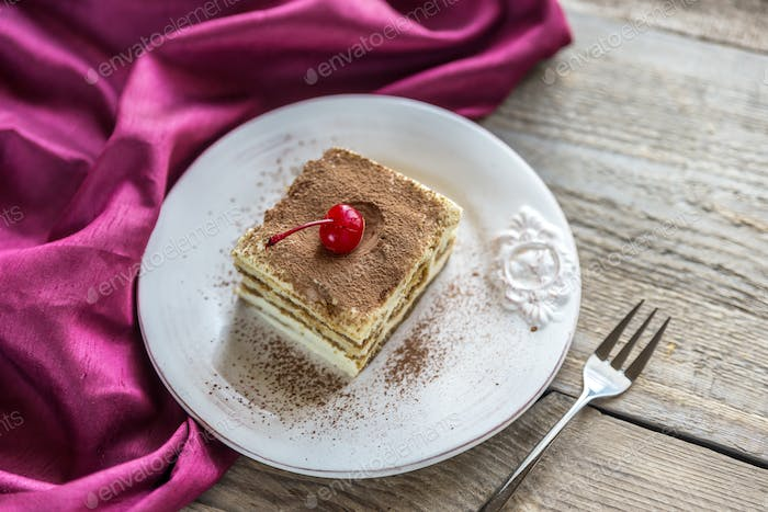 Tiramisu in the plate on the wooden background