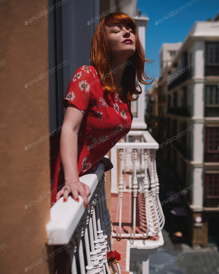 Woman in red dress eyes closed in a balcony
