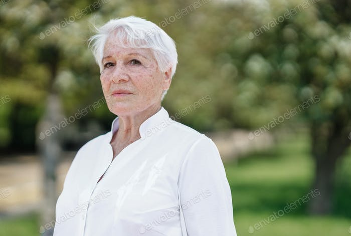 Elegant elderly gray-haired woman in the white shirt is standing in a park on a warm sunny day