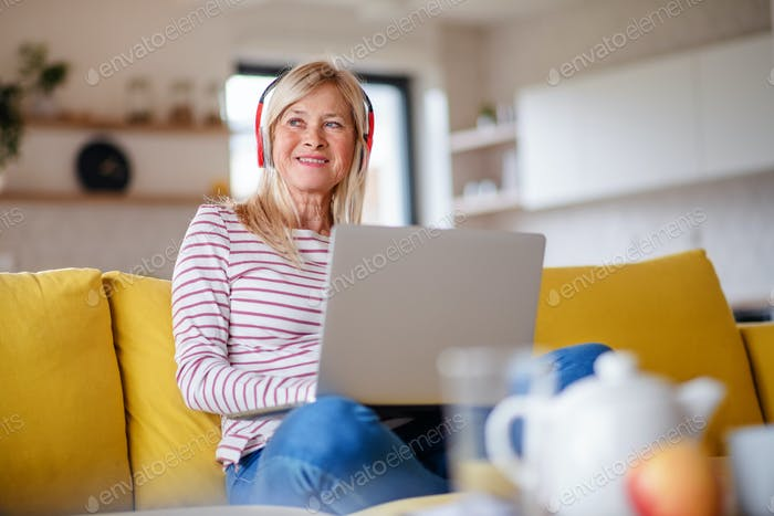 Senior woman with headphones and laptop indoors in home office, relaxing