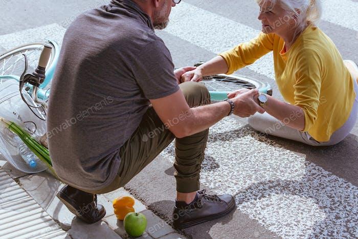 Schöner Mann hilft einer älteren Frau aufzustehen, nachdem er von einem Fahrrad auf einer Vorstadtstraße gefallen ist