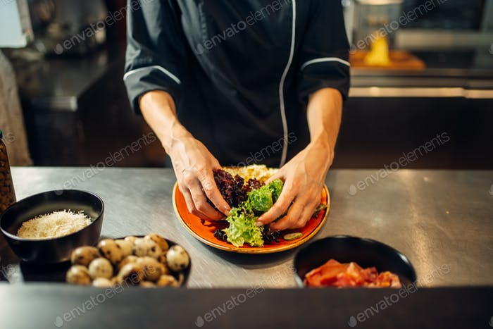 Female chef cooking meat salad on wooden table