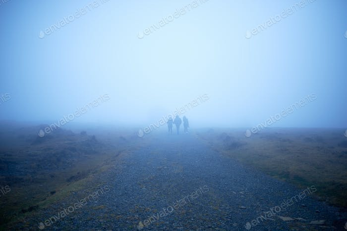 Three people walking into the fog