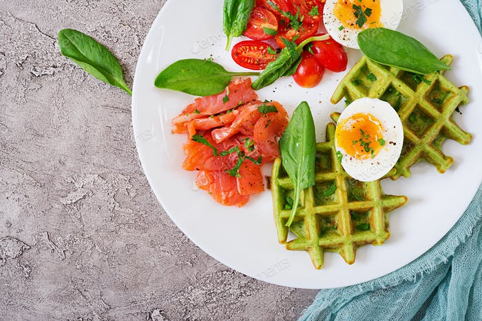 Savory waffles with spinach and egg, tomato, salmon in white plate. Tasty food. Top view. Flat lay