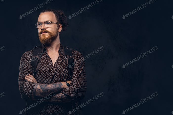 Redhead hipster student in glasses dressed in a brown shirt posing in a studio