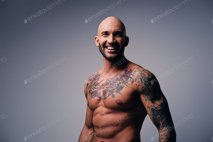 Athletic shaved head male with tattoos on his torso posing over
