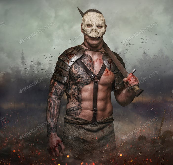Male in the skull mask holds sword in the dust batterfield background.