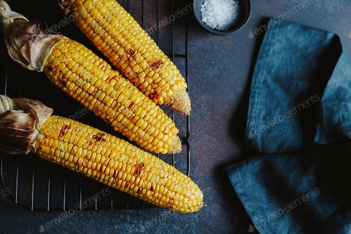 Roasted or grill corn cob with olive oil and salt on a rack