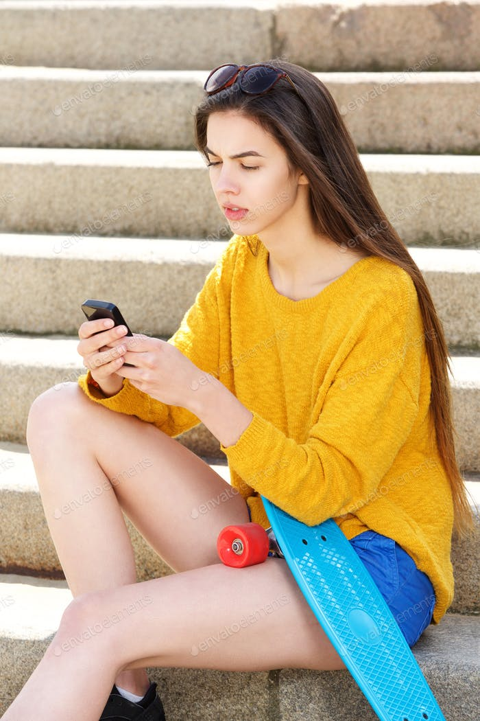 Woman sitting on steps with smart phone and skateboard