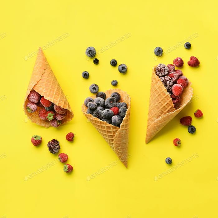Frozen berries - strawberry, blueberry, blackberry, raspberry in waffle cones on yellow background