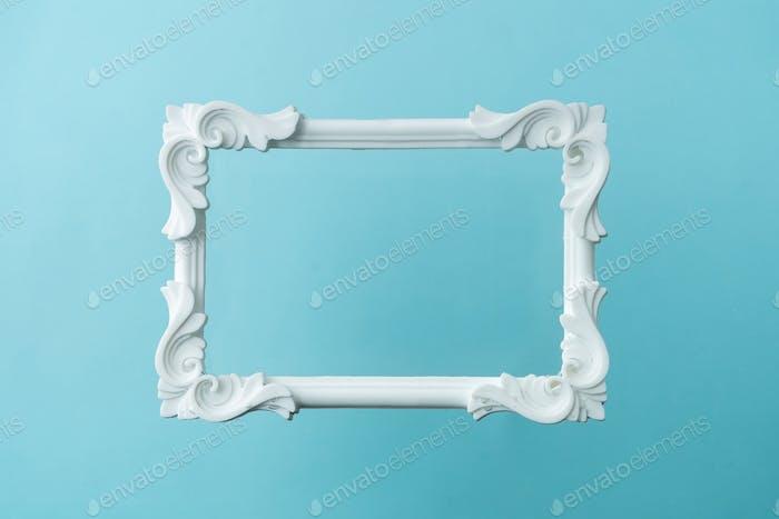 Weißer Vintage-Rahmen auf pastellblauem Hintergrund. Minimale Randzusammensetzung.