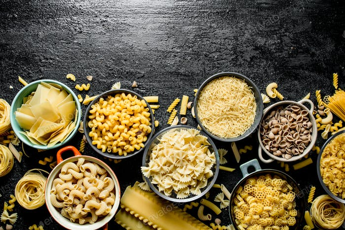 The range of different types of dry pasta in different bowls.