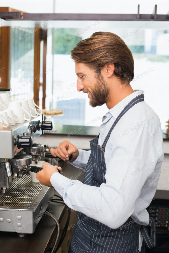 Handsome barista making a cup of coffee at the coffee shop