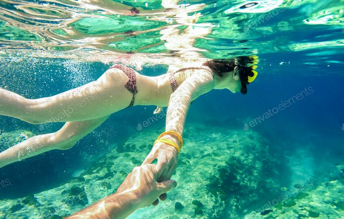 Snorkel couple swimming together in tropical sea with follow me composition