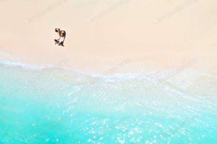 Пара прогуливается вдоль Пляжа Маврикия в Индийском океане. Вид сверху на пляж с