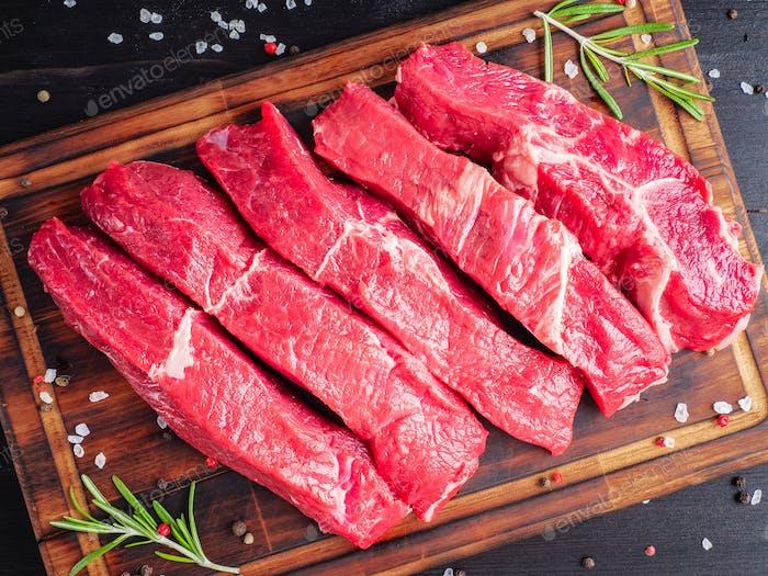 Rohes Fleisch, Rindersteak mit Gewürz auf Schneidebrett auf dunklem Hintergrund mit Rosmarin,