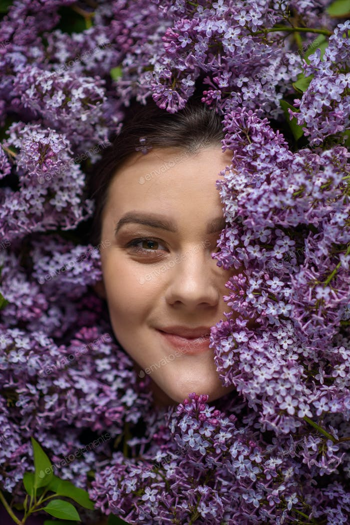 Portrait of a young woman surrounded by lilacs.