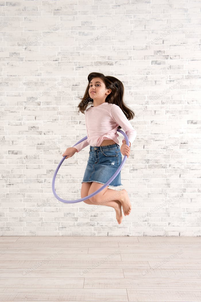 Girl playing with hula hoop in bright room