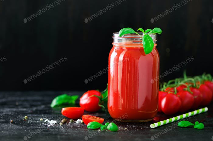 Organic fresh tomato juice in a glass jar, basil, cherry, salt, pepper and straw on dark black