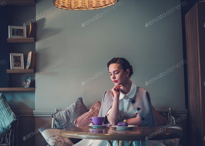 Elegante joven dama sola en un café