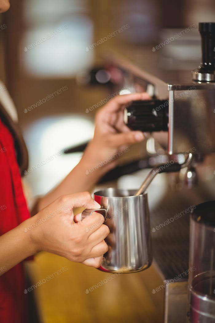 Barista steaming milk at the coffee machine at the coffee shop