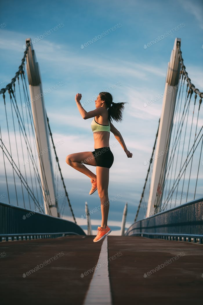 Young fit blonde woman jumping on the bridge