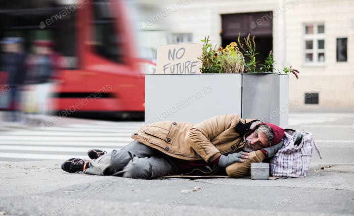 Homeless beggar man lying on the ground outdoors in city asking for money donation.