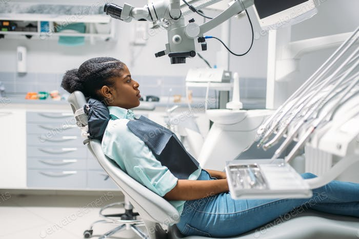 Female patient on chair, visit in dental clinic