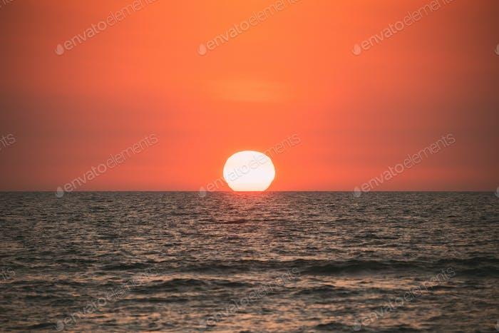 Natural Color Sunset Sunrise Sky Over Sea. Seascape With Shining Setting Sun On Sea Horizon