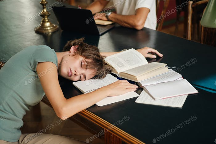 Young tired female student sleeping on desk with books around during study in library of university