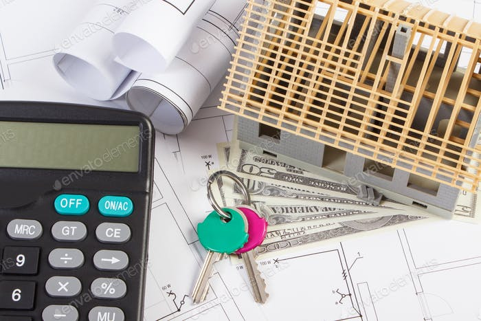 House under construction, keys, calculator and currencies dollar on electrical drawings