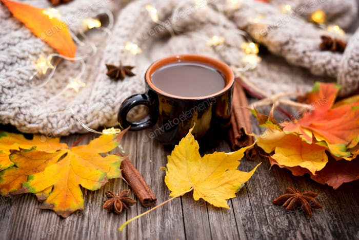 Autumn composition. Fall leaves, cup of coffee and scarf on old