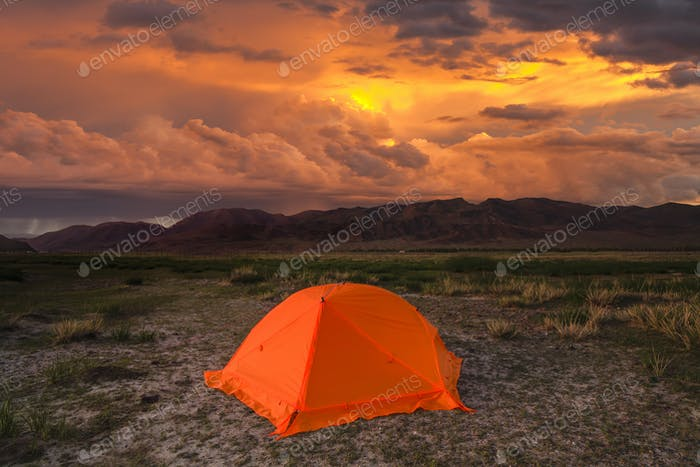 Red tent in the mountains on a sunset background