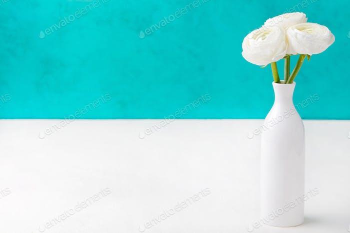 Weiße Ranunkelblüten in einer Keramikvase