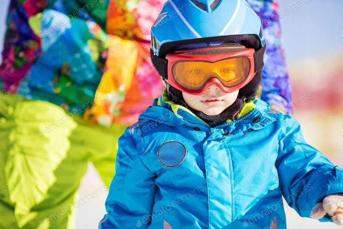 Little skier wearing ski helmet and goggles