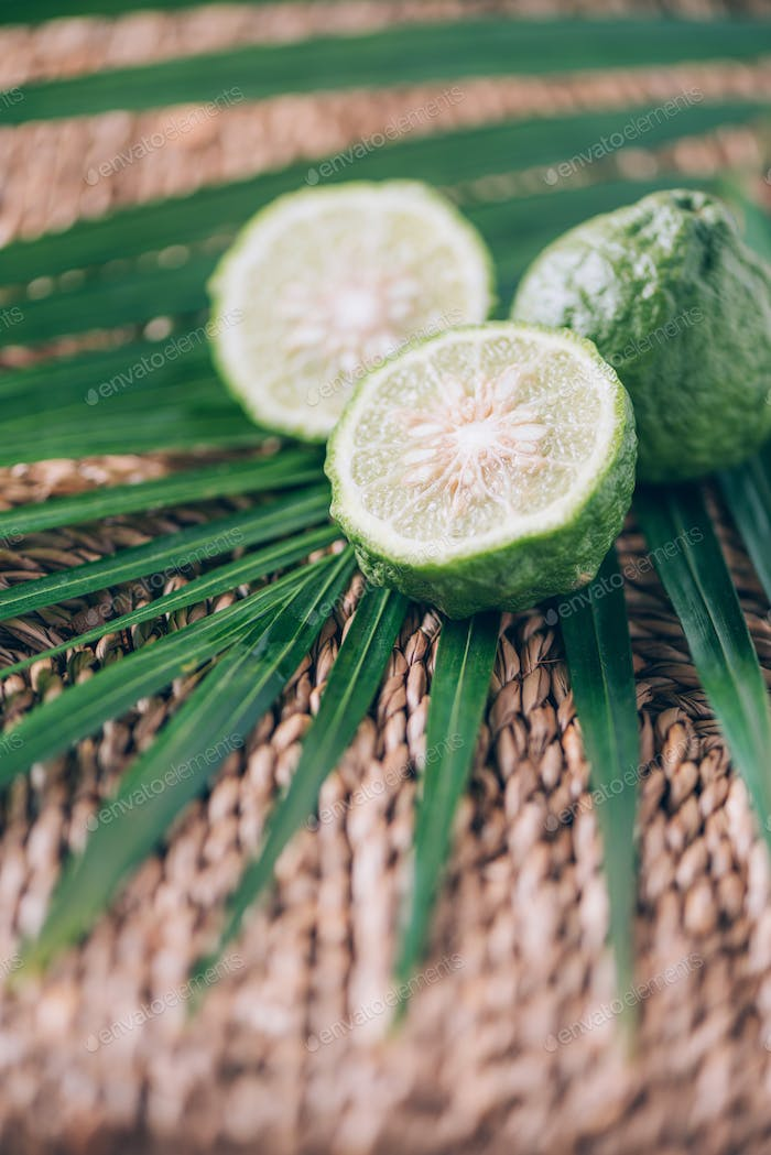 Fresh ripe limes over palm leaves on rattan background. Copy space. Acca sellowiana. Creative design