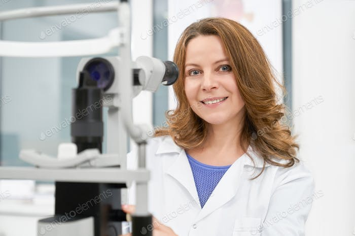 Doctor optometrist in white coat posing with slit lamp
