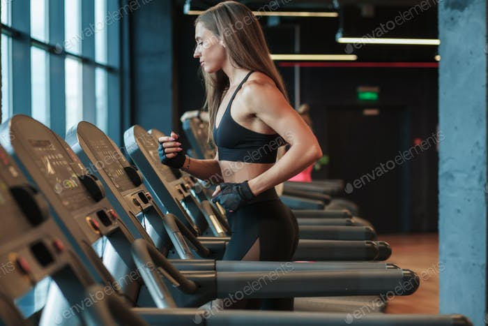 sporty female run on treadmill in gym