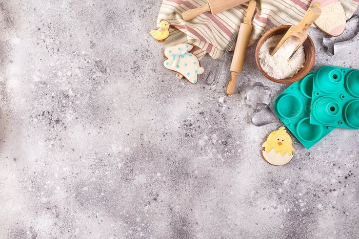 Baking accessories on stone background with flour and easter glazed cookies . Easter preparation or