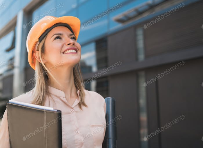 Professional architect woman standing outdoors.