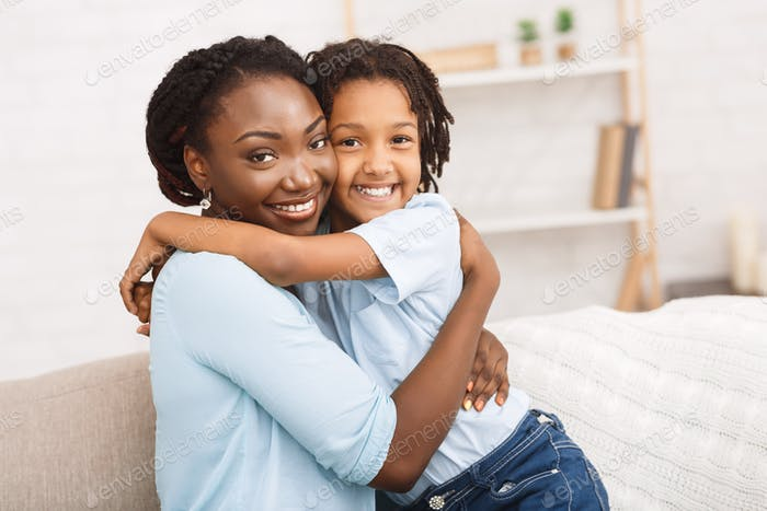 Black mother and daughter hugging at home