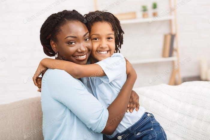 schwarze Mutter und Tochter umarmt zu Hause