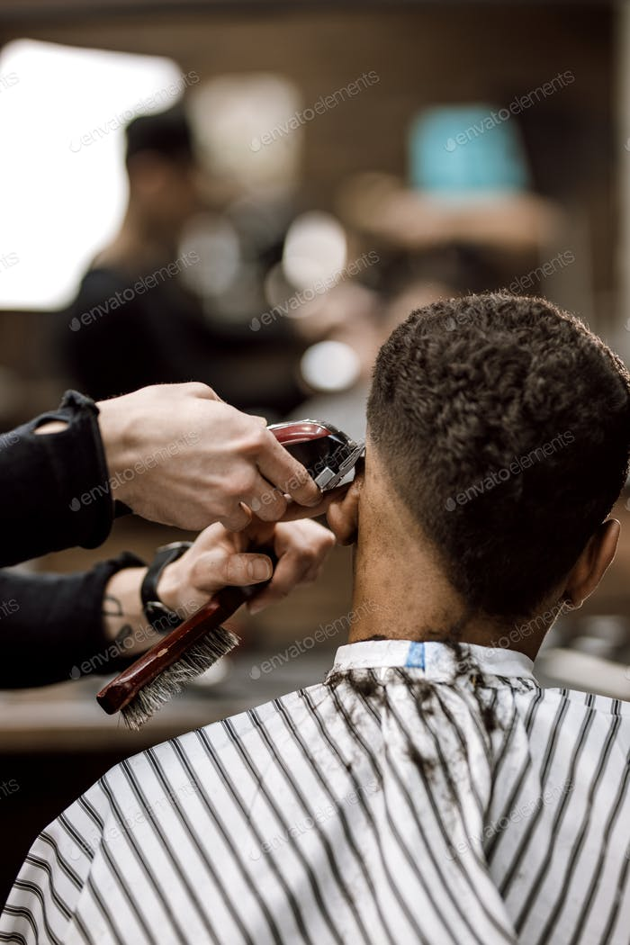 The barber makes a razor cut hair back and sides for a stylish black-haired man sitting in the