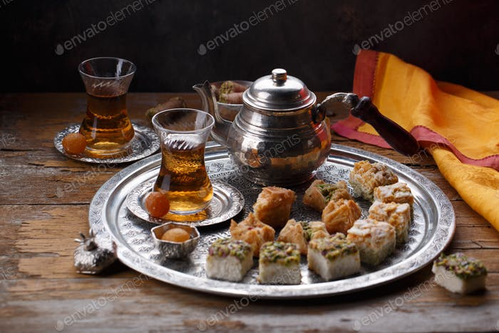 Oriental sweets and turkish tea on a copper plate, copy space