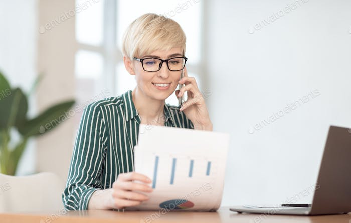 Businesswoman Talking On Cellphone Holding Documents Sitting At Workplace