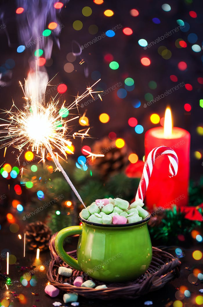 Green mug of hot chocolate with marshmallows, candy cane and spa