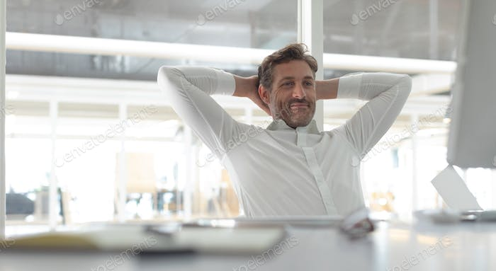 Happy Caucasian business male executive with hands behind hand sitting at desk