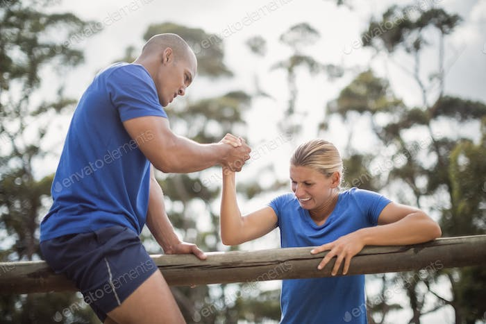Man assisting woman to climb a hurdles during obstacle training